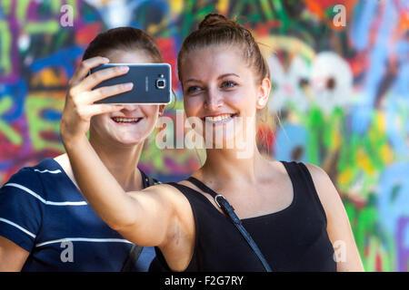 Two smiling women are taking a selfie in front of John Lennon Wall Prague, Kampa, Czech Republic, Europe - Stock Photo