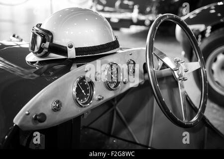 helmet and glasses resting on a old vintage sports car - Stock Photo