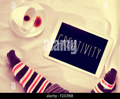 high-angle of the feet of a man wearing striped socks, a cup of coffee and a tablet computer with the word creativity - Stock Photo