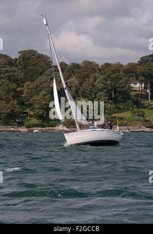 Sailing Yacht Under Sail leaning In The Wind On THe River Fal Cornwall England UK - Stock Photo