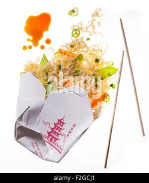 chinese to go noodles coming out of container with soy sauce and chopsticks, back lit on white - Stock Photo