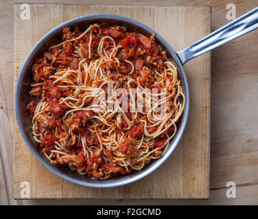 looking straight down on pasta bolognese in pan - Stock Photo