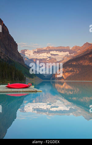 Red canoes at glacial Lake Louise with Victoria glacier, Banff National Park, Alberta, Canada