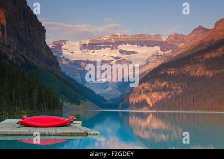 Red canoes at glacial Lake Louise with Victoria glacier, Banff National Park, Alberta, Canada - Stock Photo