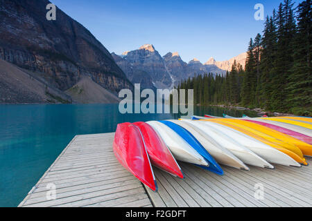 Colourful canoes at Moraine Lake in the Valley of the Ten Peaks, Banff National Park, Alberta, Canada - Stock Photo