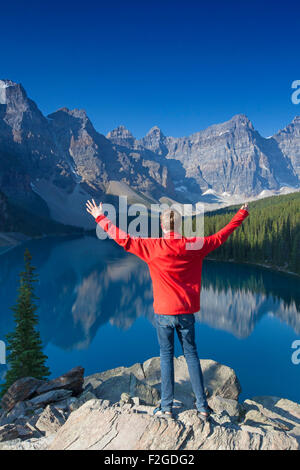 Tourist with open arms on look-out point looking over Moraine Lake in the Valley of the Ten Peaks, Banff NP Alberta, - Stock Photo