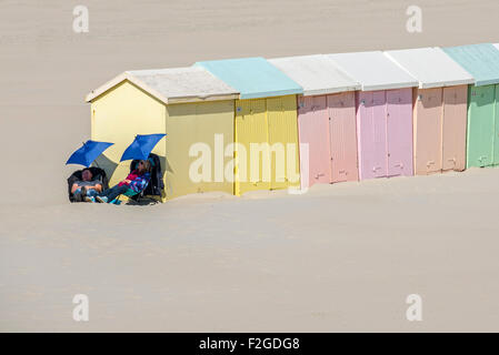 Two day trippers asleep under sunshades next to pastel coloured beach cabins / huts, Berck / Berck-sur-Mer, Côte - Stock Photo