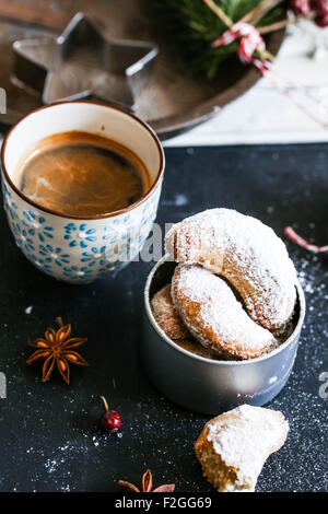 Vanillekipferl (crescent-shaped vanilla biscuits) being topped with vanilla sugar - Stock Photo