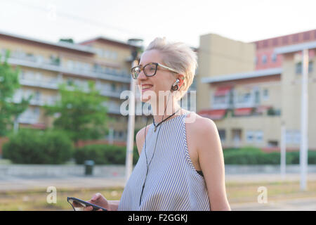 half length of young handsome caucasian blonde designer listening music with earphones, overlooking right, smiling - Stock Photo
