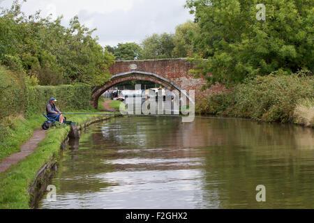 Angler pole fishing close to bridge along Staffordshire and Worcestershire Canal near Penkridge. UK - Stock Photo