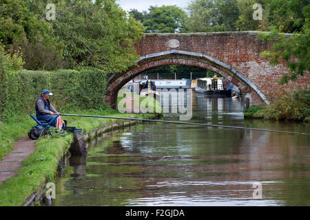 Single angler pole fishing with bridge and narrow boats in the background. Staffordshire and Worcestershire Canal - Stock Photo