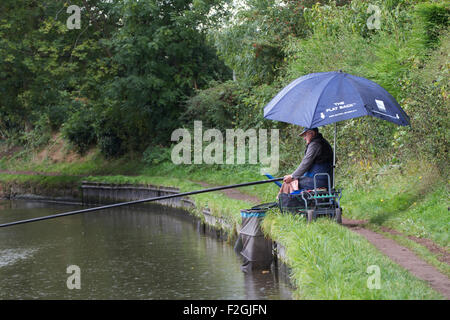 man pole fishing the rain near Penkridge on the Staffordshire and Worcestershire canal, - Stock Photo