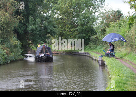 Barge and fisherman along the Staffordshire and Worcestershire Canal near Penkridge. UK - Stock Photo