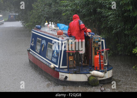 Canal boat on the Staffordshire and Worcestershire Canal in heavy rain. Penkridge. UK - Stock Photo