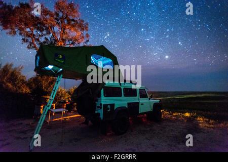 Land Rover parked with a pop up tent on its roof under the night sky in Botswana, Africa - Stock Photo