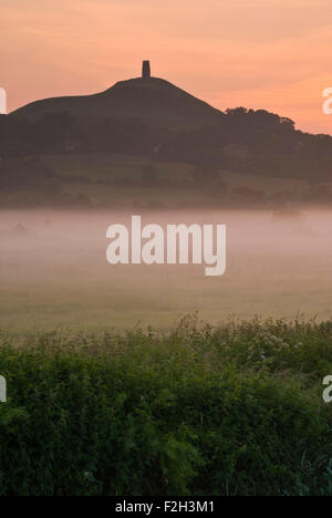 Glastonbury Tor rises out of the early morning mist in Somerset, England, UK. - Stock Photo