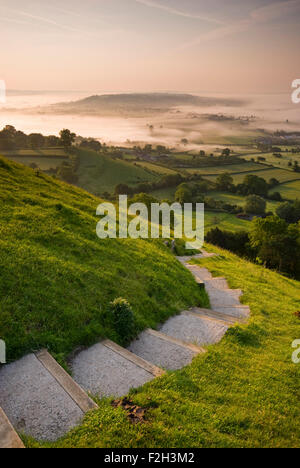 View down the steps leading from the top of Glastonbury Tor, looking towards the morning mist in Somerset, England, - Stock Photo