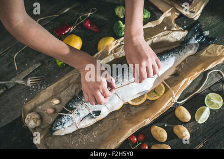 Tying a rope on fish for grilling. Baking paper - Stock Photo