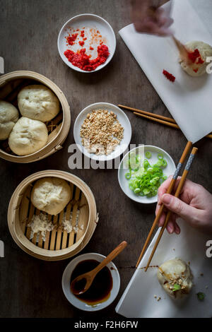 Two hands eating Asian street food with chopsticks on wooden tabletop with bamboo steamers. Top view - Stock Photo