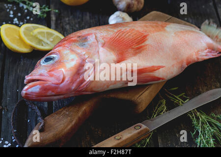 Raw fish grouper on wooden cutting board with sliced lemon, rosemary and saltover old wooden kitchen table. Dark - Stock Photo