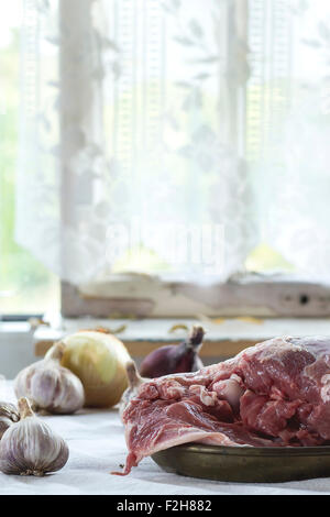 Raw loaf of lamb with onions over white kitchen table. With window as background. Rustic style. - Stock Photo