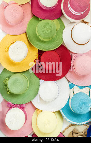 Variety of colored straw hats hanging on a wall in the market - Stock Photo