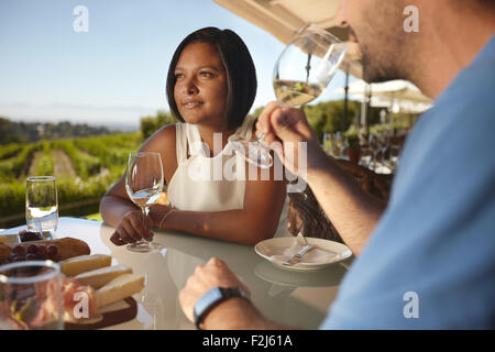Young woman with a man drinking wine. Couple on vacation in outdoor wine bar restaurant by a vineyard. - Stock Photo