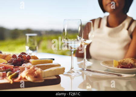 Table set in the winery with two glasses of wine, cheese and grapes. Woman sitting in back at winery restaurant - Stock Photo
