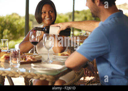 Happy young woman sitting at table with man pouring a glass of red wine at winery restaurant. - Stock Photo