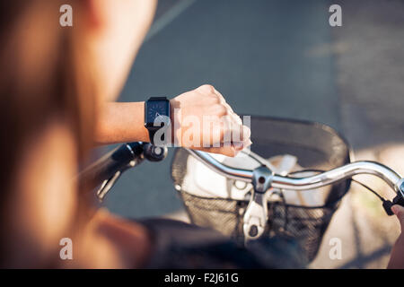 Hand of a woman with smartwatch. Close up shot of female on bicycle checking time on her smart wristwatch. - Stock Photo