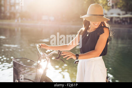 Attractive young woman wearing hat at the park with her bicycle. Beautiful female model looking down smiling. - Stock Photo