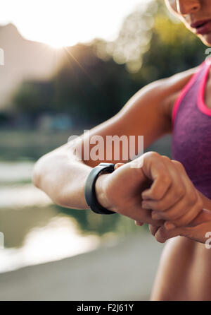 Close up shot of young woman jogger ready to run set and looking at sports smartwatch. Fitness female checking her - Stock Photo