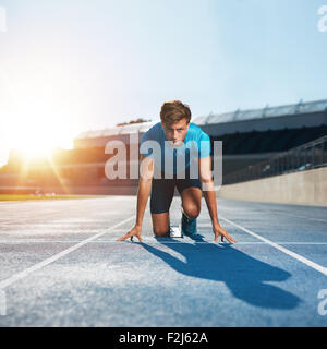 Fit and confident man in starting position ready for running. Male athlete about to start a sprint looking at camera - Stock Photo