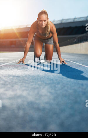 Young woman sprinter in the starter position on a race track at a sports stadium looking up at camera with determination. - Stock Photo