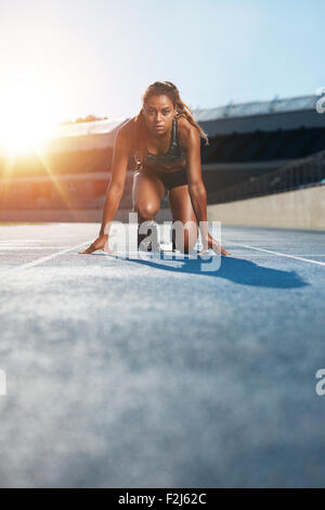 Vertical shot of young female sprinter taking ready to start position facing the camera.  Woman athlete in starting - Stock Photo