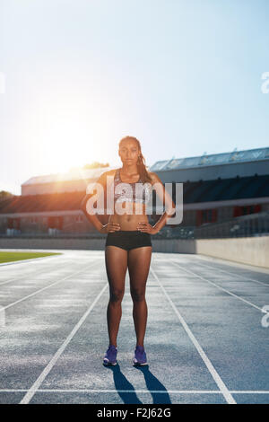 Full length outdoor shot of african young woman on stadium preparing herself for a run. Professional female athlete - Stock Photo