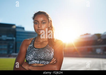 Portrait of confident young sportswoman standing with her hands folded on athletics stadium looking at camera with - Stock Photo