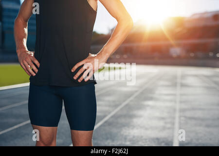 Mid section shot of male athlete standing on race track with his hands on hips on a bright sunlight. Cropped shot - Stock Photo