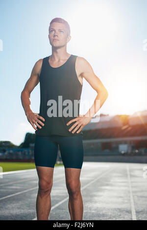 Fit young man standing with his hands on hips looking away. Determined male athlete preparing for a run on athletics - Stock Photo