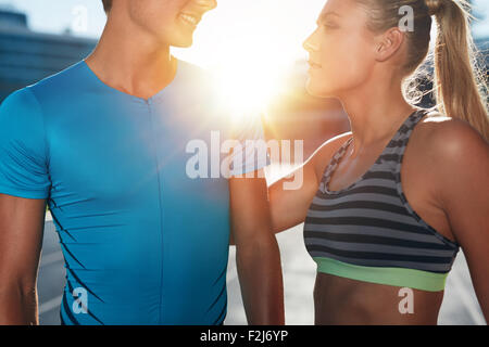 Closeup shot of two young athletes standing on stadium race track on a bright sunny day. Man and woman in sports - Stock Photo
