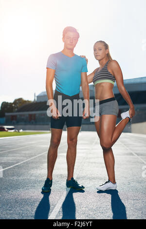 Full length shot of young man and woman standing on athletics race track on a bright sunny day. Fit athletes on - Stock Photo