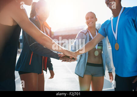 Shot of a group of young sportsmen with medals piling their hands while standing in a huddle. Successful team of - Stock Photo