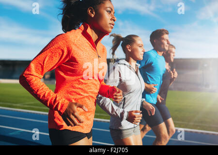 Young african woman running with her team on running track in stadium. Multiracial team of runner practicing at - Stock Photo