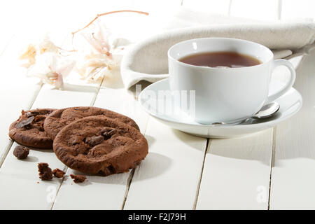 chocolate cookies on a white wooden table in a relaxing autumn environment - Stock Photo