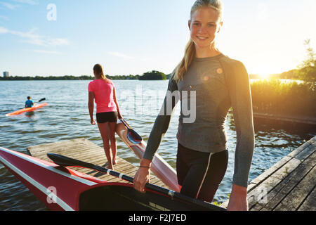 Fit woman with a kayak getting ready for practice - Stock Photo