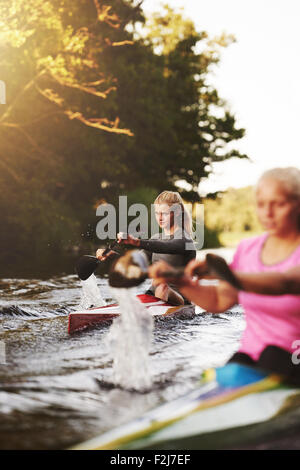 Two woman racing in kayaks on a lake - Stock Photo