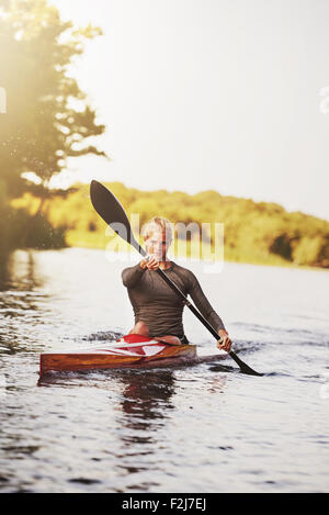Athletic young blond woman sitting in the kayak while paddling with a double-bladed paddle on the still surface - Stock Photo