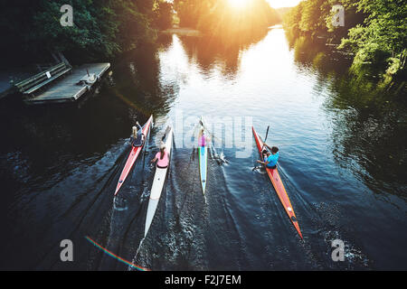 Team of rowing people racing in the sunset - Stock Photo