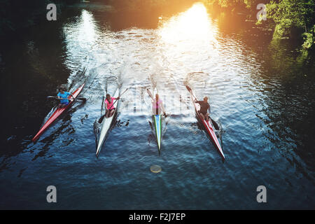 Team of rowing people sailing against camera in sunset - Stock Photo