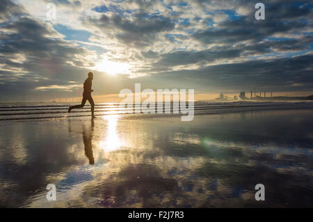 North Gare beach near Seaton Carew, UK. 20th September, 2015. Weather: early morning jogger   at sunrise on Sunday - Stock Photo